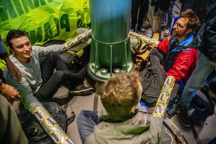 Actievoerders van Greenpeace klinken zich vast aan de palen van Schiphol Plaza.
