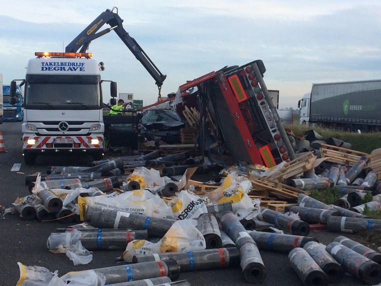 De gekantelde vrachtwagen en de rollen roofing op de snelweg.