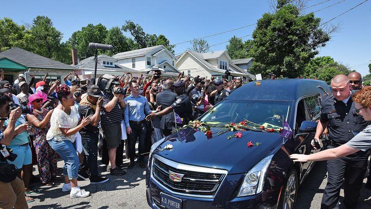 Omringd door agenten wordt de begrafenisauto met het lichaam van Muhammad Ali langs zijn ouderlijk huis gereden - de roze woning met de drie raampjes. Beeld null