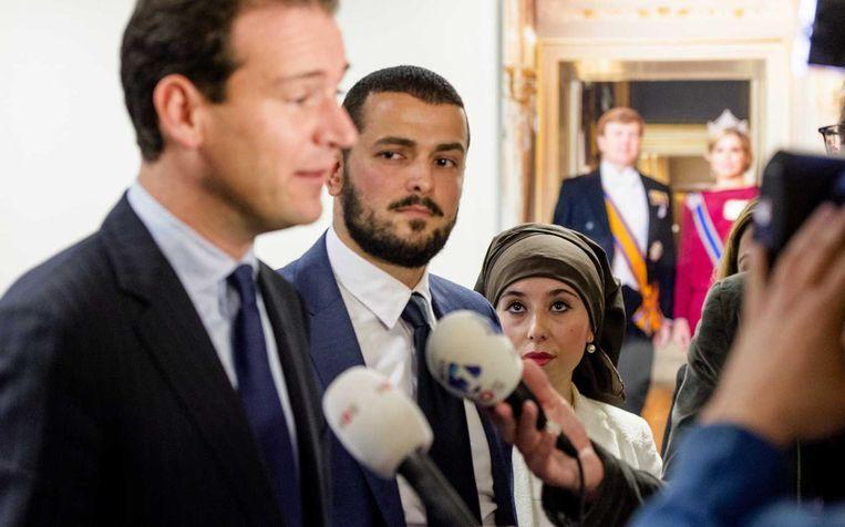 Cemil Yilmaz (M), woordvoerder van een groep Turkse jongeren, kijkt toe hoe minister Lodewijk Asscher (L) van Sociale Zaken op zijn ministerie de pers toespreekt. De jongeren bieden de minister een petitie aan naar aanleiding van zijn reactie op een onderzoek naar steun van Turkse jongeren aan IS. Beeld anp