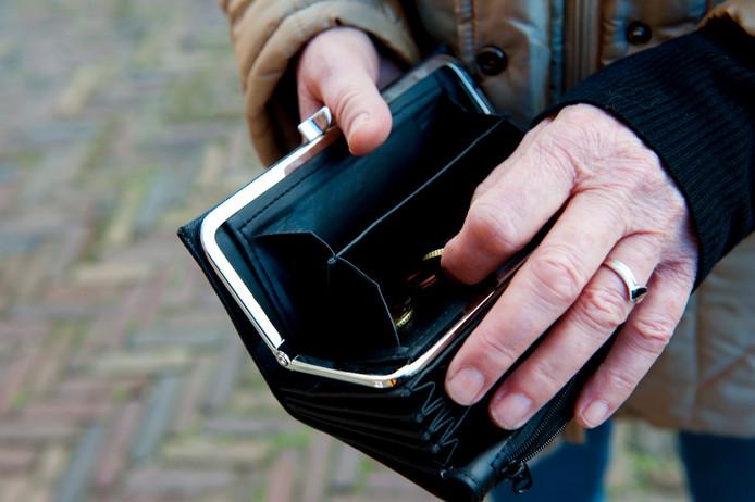 Oudere zoekt naar geld in haar portemonnee