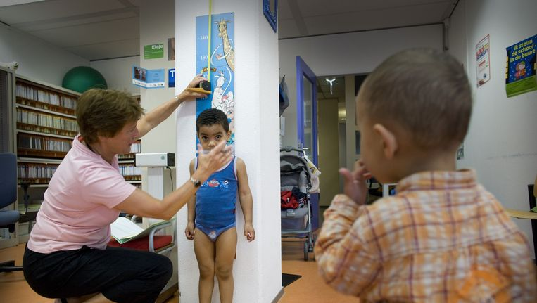 Twee jonge kinderen worden gecontroleerd door een medewerker van het consultatiebureau. Beeld null