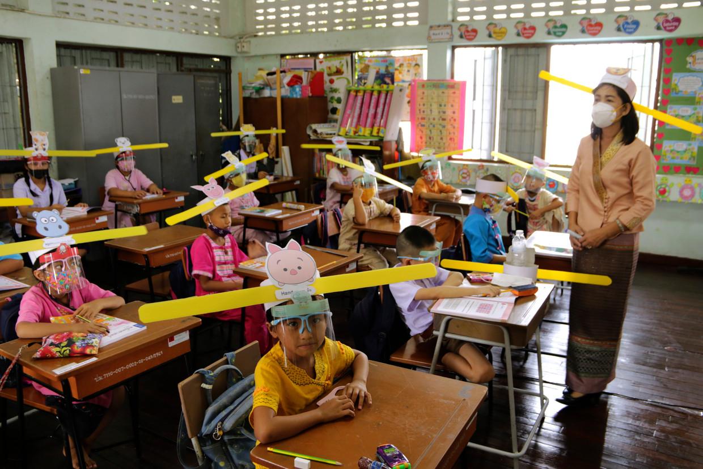 Een klas in Thailand heeft speciale hoedjes gemaakt om aan te geven hoeveel afstand moet worden gehouden.  Beeld AP