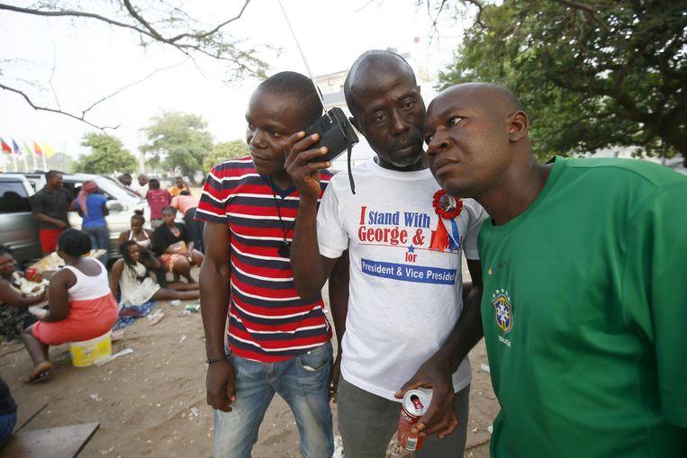 Aanhangers van de CPC beluisteren de verkiezingsuitslag in Liberië. Beeld anp