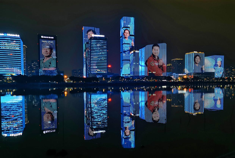 Zorgverleners uit de Chinese stad Fuzhou die naar coronabrandhaard Wuhan zijn uitgezonden worden groot op de wolkenkrabbers uitgebeeld om ze te eren.  Beeld AFP