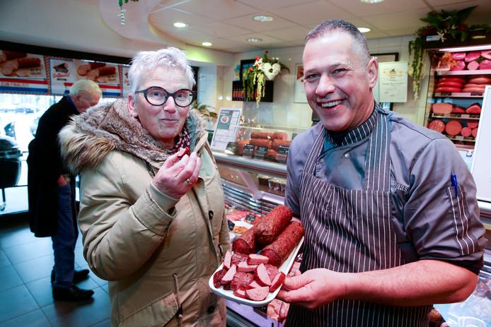 Vaste klant Teunie Schaap weet natuurlijk allang hoe de grillworst smaakt, maar grijpt toch haar kans als eigenaar Rien Baas het prijswinnende product uitdeelt om te proeven.