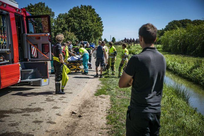 Ambulancepersoneel schiet de vrouw te hulp.