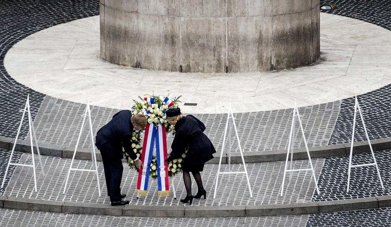 Koning Willem-Alexander en koningin Maxima leggen een krans bij het Nationale Monument op de Dam tijdens de nationale dodenherdenking. Beeld ANP