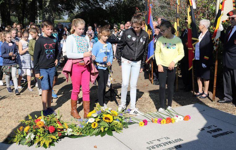Leerlingen leggen bloemen neer aan de begraafplaats.