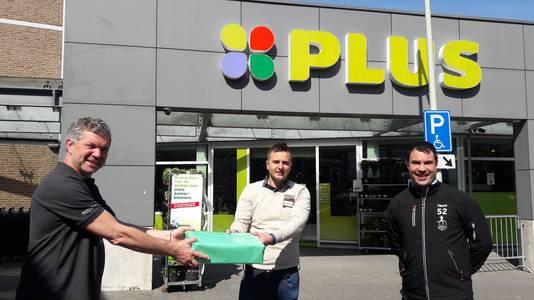 Voorzitter Peter van der Graaf (links) van Roparunteam Altijd Eentje Te Veel overhandigt een cadeau aan sponsor Rik Linssen van de Plus in Halsteren, rechts penningmeester Christiaan van der Vlugt van AETV.