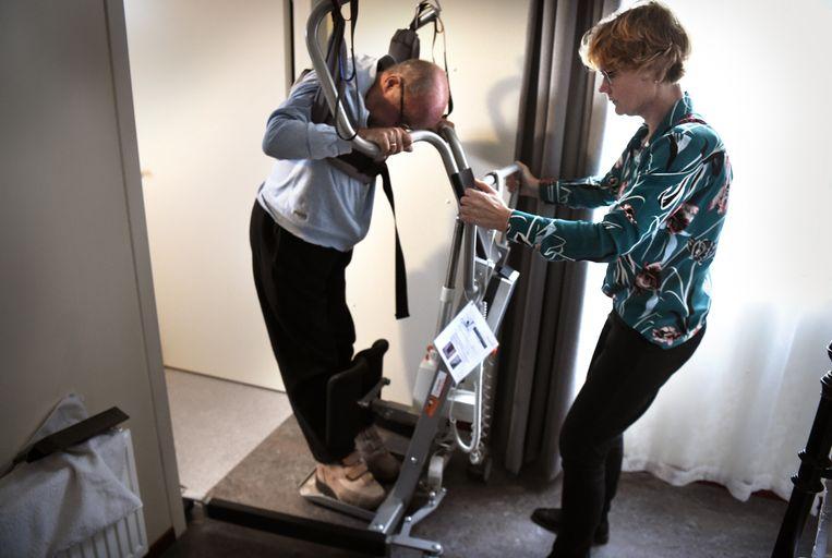 ZZP-er in de zorg Karin de Jager helpt een ALS-patient bij hem thuis. Beeld Marcel van den Bergh