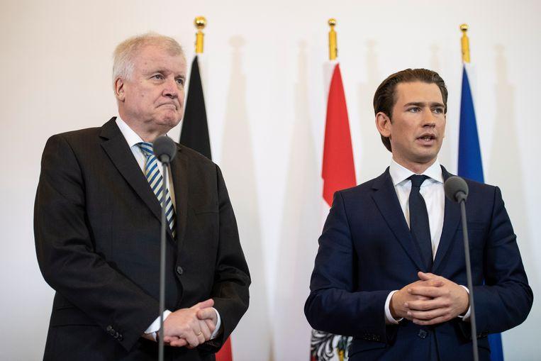 Het knettert tussen Duitsland en Oostenrijk over het migratiebeleid. De gezichten van de Duitse minister van binnenlandse zaken Horst Seehofer (L) en de Oostenrijkse kanselier Sebastian Kurz staan strak tijdens hun gezamenlijke persconferentie, donderdag. Beeld EPA