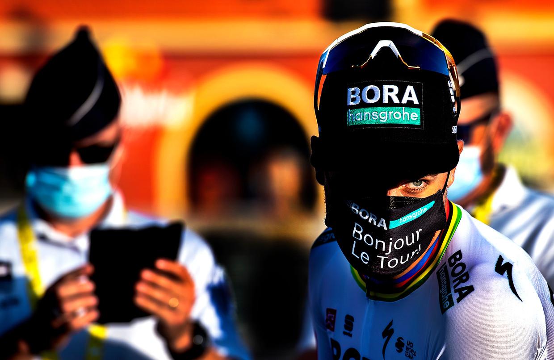 Peter Sagan, met mondkapje ( Bonjour Le Tour!), staat in de avondzon klaar voor de ploegenpresentatie.  Beeld Klaas Jan van der Weij / de Volkskrant