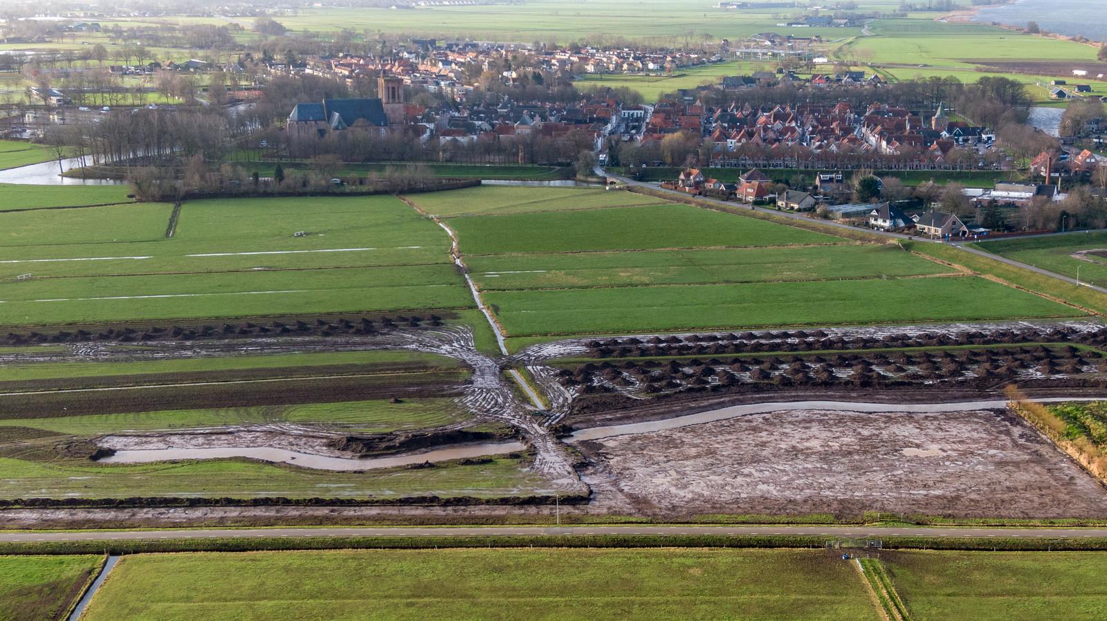 Langs de Hellenbeekstraat (onder) wordt de oude loop van de Hellenbeek uitgegraven. Op de achtergrond de monumentale vesting van Elburg.