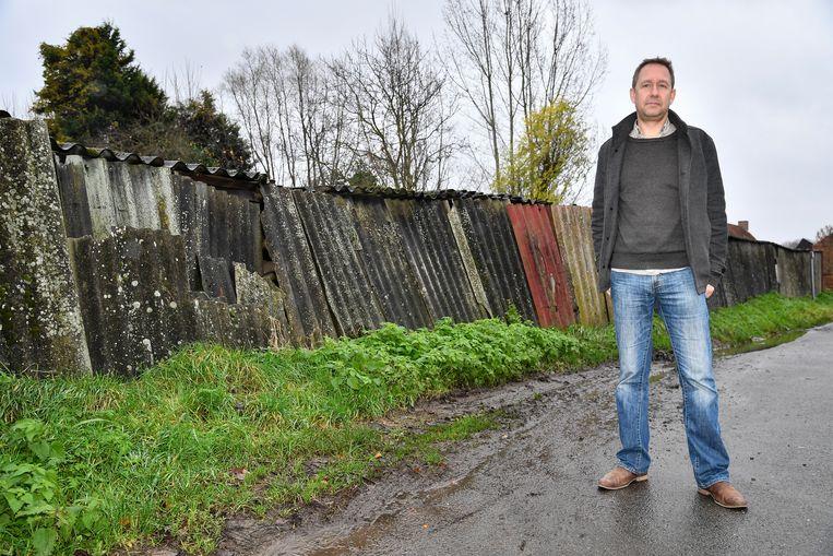 """Tom Bogman bij de kapotte afsluiting met asbest. """"De stad moet dringend actie ondernemen"""", zegt hij."""