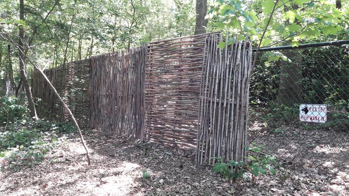 Om te voorkomen dat scoutingkinderen te zien zijn op de bewakingsbeelden van de buurman, heeft scouting een een haag van dunne boomstammetjes geplaatst.