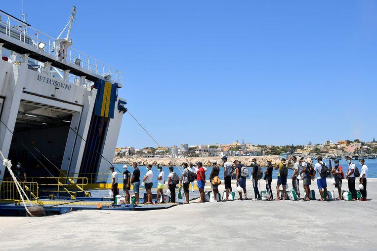Migranten worden begeleid naar het opvangcentrum. Beeld AFP