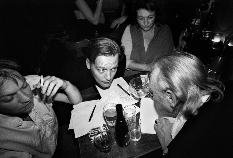 Schrijver Erik Jan Harmens (midden) is jurylid bij een poëziefestival in het Amsterdamse café Festina Lente, waar aanstormende dichters voordragen uit eigen werk.  Beeld Hollandse Hoogte / Marieke van der Velden