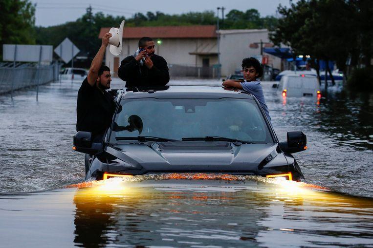 Sommige Texanen slagen erin zich in veiligheid te brengen met hun eigen auto. Vele andere auto's en vrachtwagens zijn onder water komen te staan en werken niet meer. Beeld REUTERS