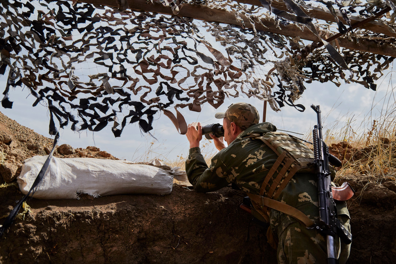 Een Oekraïense militair kijkt op 2 oktober 2020 in Verchnotoretske, Oekraïne, naar door Rusland gesteunde jagers aan de frontlinie buiten Donetsk.