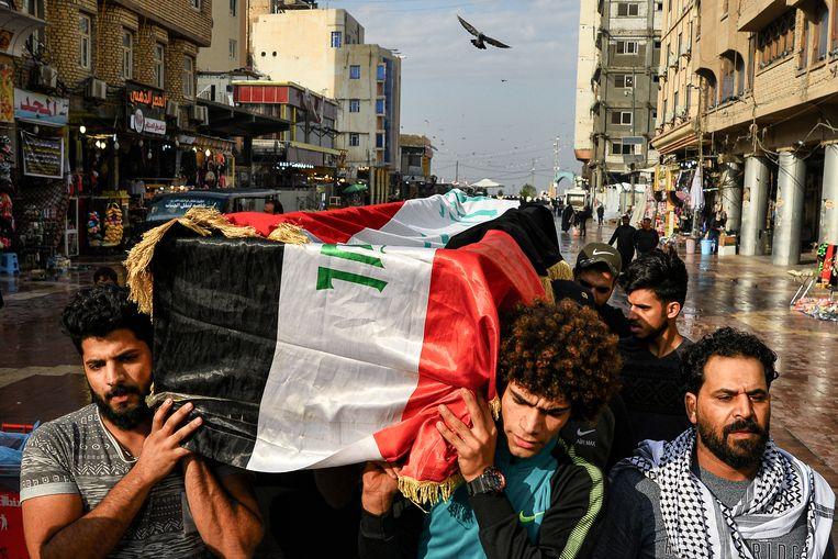 Irakezen dragen de kist van een van de doodgeschoten betogers door de straten van Najaf.  Beeld AFP