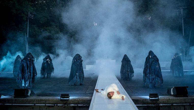 Mannen in zwarte capes hebben Caesar dodelijke dolksteken toegebracht. Op de achtergrond zwiepen bomen onheilspellend. Beeld Ben van Duin