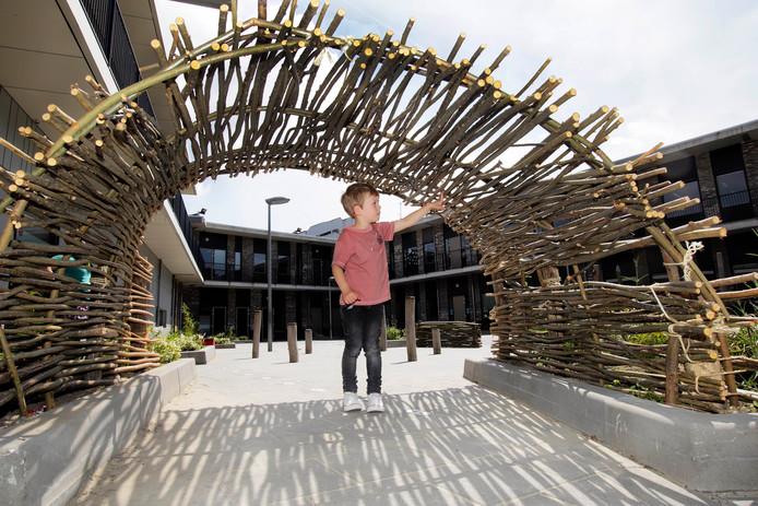 Een jongen bekijkt vol bewondering de stokkentunnel, gemaakt van boomtakken.  In De Vleer zijn basissschool De Hofstee , basisschool De Springplank en kinderdagverblijf Kober gevestigd.