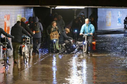 Fietsers lopen door de overstroomde Berekuil.
