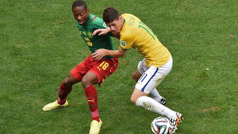 Enoh Eyong (L) van Kameroen in duel met Oscar Vie van Brazilie tijdens het WK. Beeld anp