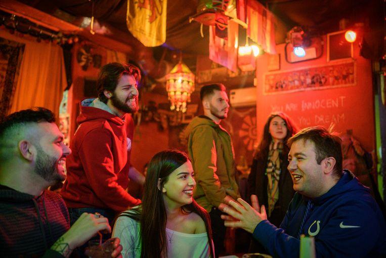 Armen Rostamian (links, zittend) en Antranig Vartanian (rechts) uit Syrië in een bar in hoofdstad Jerevan. Beeld Yuri Kozyrev