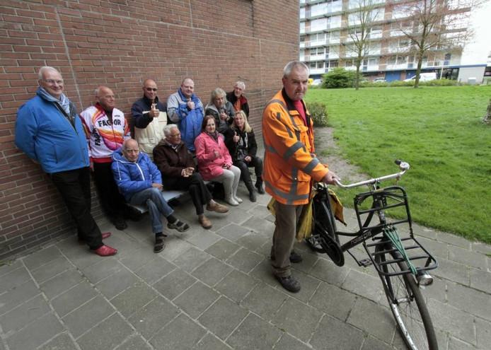 Bewoners voeren actie om Cok Machielsen (fiets) in de Akeleiflat te houden. Ze roemen zijn werk als vrijwillig vuilprikker. Het bankje werd door zijn inspanning naar een betere plek verplaatst.