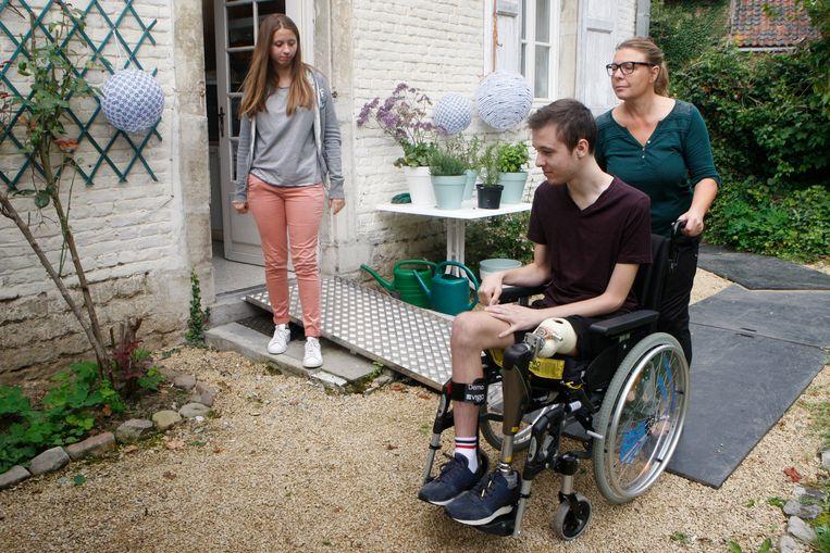 Mama Cindy helpt haar zoon over de kiezels te manoeuvreren in zijn gewone rolstoel. Vriendin Cindy kijkt toe.