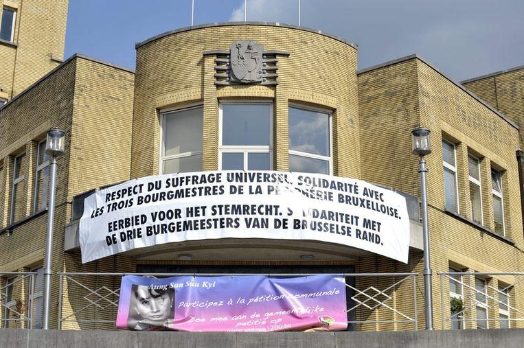 Olivier Maingain drukt via een groot spandoek aan de gevel van zijn gemeentehuis in Sint-Lambrechts-Woluwe zijn steun uit voor de drie niet-benoemde burgemeesters.