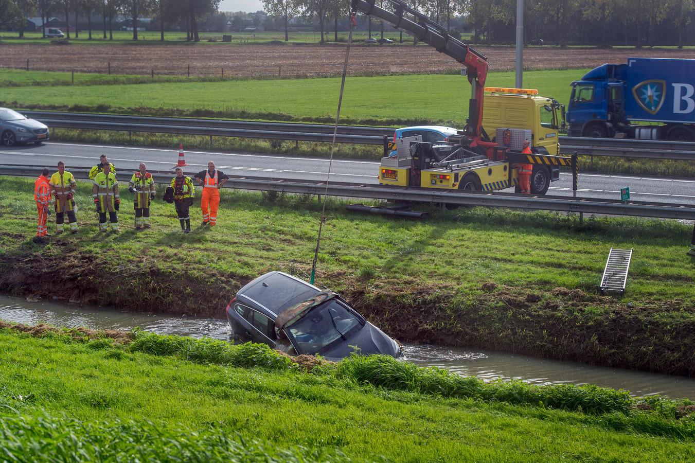 Een takelwagen takelt de auto uit de sloot langs de A73 bij Beuningen.