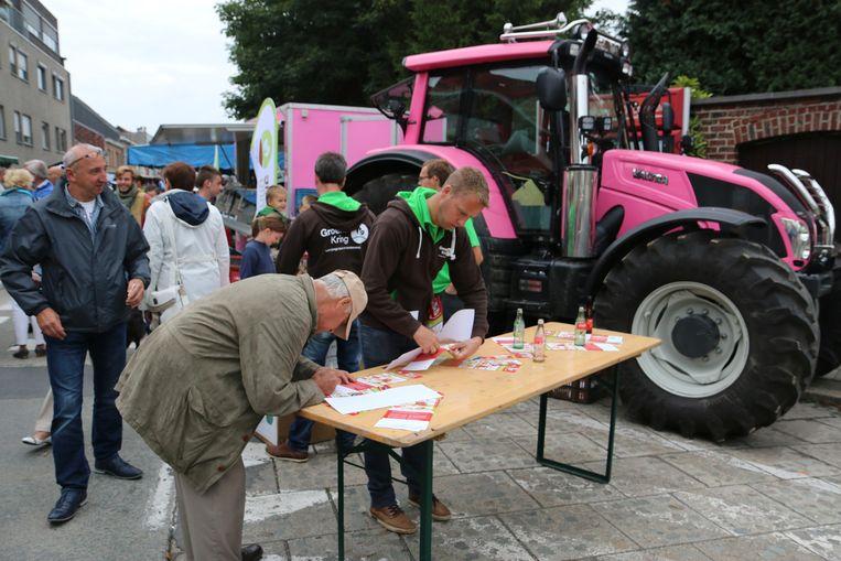 Een bezoeker ondertekent de petitie van Groene Kring. Op de achtergrond is de tractor Roza te zien.
