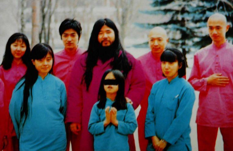 Shoko Asahara (C) met zijn vrouw Tomoko (linksvoor) en dochter Archery (midden voor haar vader) samen met een groep discipelen.
