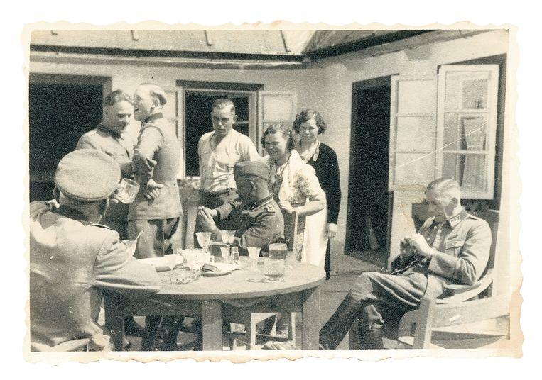 Deel van de kampstaf, borrelend voor de kantine in het Vorlager, met vermoedelijk geroofde kristallen glazen. Op een steenworp afstand lagen de gaskamers. Johann Niemann is de derde van links. Beeld United States Holocaust Museum