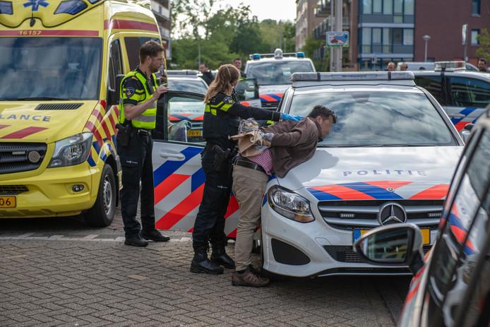 Agenten arresteren de man die in een flat aan de Alphense Diamantstraat enkele gezinsleden neerstak.