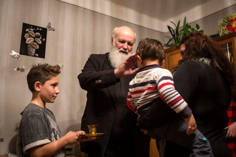 Predikant Gábor Iványi doopt een meisje en een jongen tijdens zijn bezoek aan het gezin in het Roma-dorp Gyöngyöspata. Beeld Julius Schrank