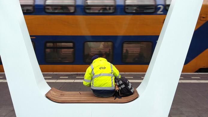 Een medewerker van de Nederlandse Spoorwegen wacht op de trein op een van de perrons van station Arnhem Centraal.