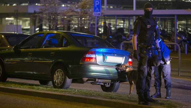 Leden van de marechaussee onderzoeken een auto met Belgisch kenteken op luchthaven Schiphol. Beeld anp