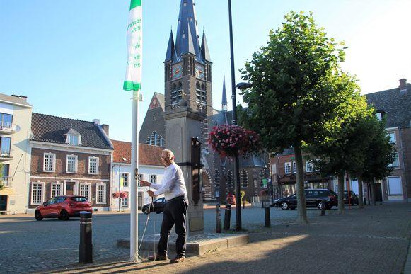 Rik Rijcken, de burgemeester van Hamont-Achel, hijst de vlag in zijn stad.
