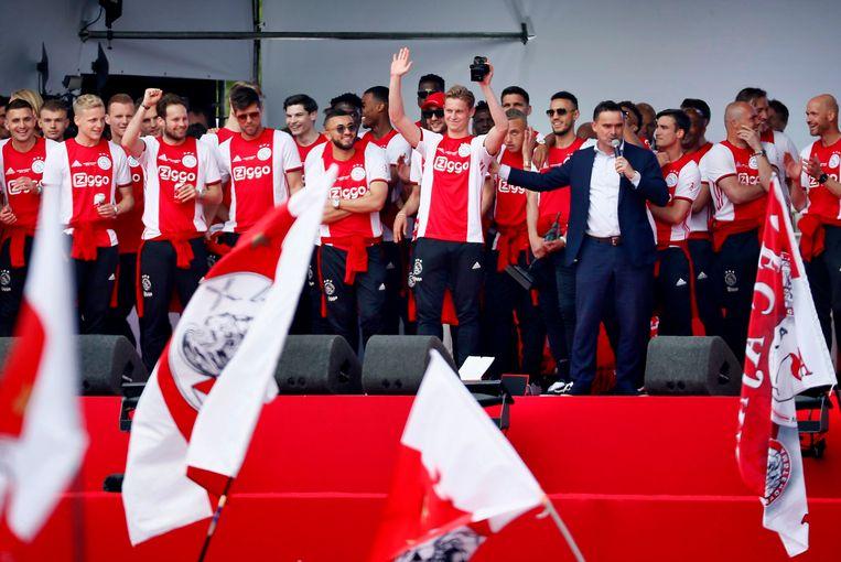 Frenkie de Jong, Marc Overmars en spelers van Ajax op het podium tijdens de huldiging van de 34ste landstitel op het Museumplein.  Beeld ANP