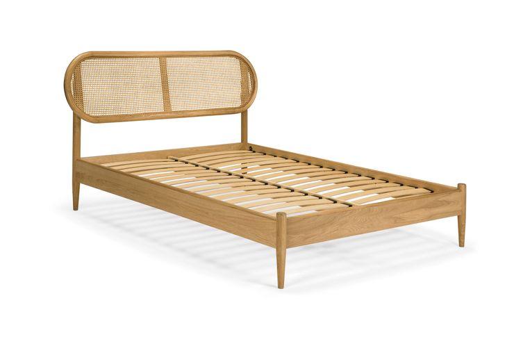Eikenhouten tweepersoonsbed 'Rema' is voorzien van een rieten hoofdbord, € 799. made.com Beeld