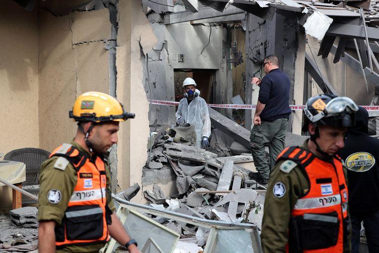 Israëlische politieagenten en soldaten bezoeken maandagochtend een huis in Mishmeret dat is verwoest door een raketaanval.