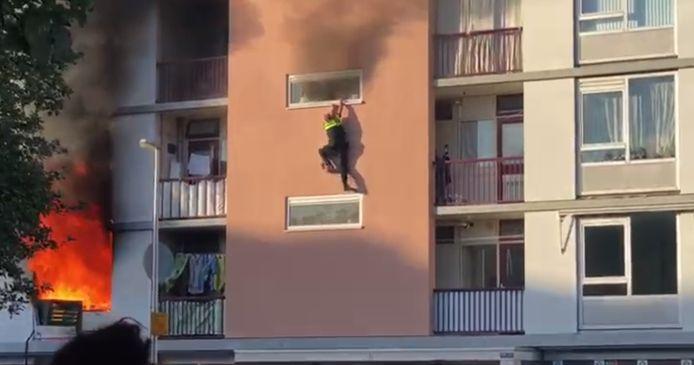 Agent Zefanja Engberts hangt uit het raam van brandende flat Kanaleneiland.