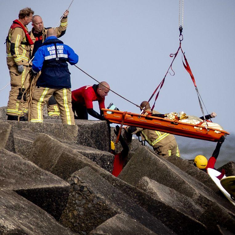Hulpverleners bergen een lichaam dat gevonden werd tijdens de hervatte zoektocht naar de vermiste watersporters bij het Noordelijk Havenhoofd. Beeld ANP