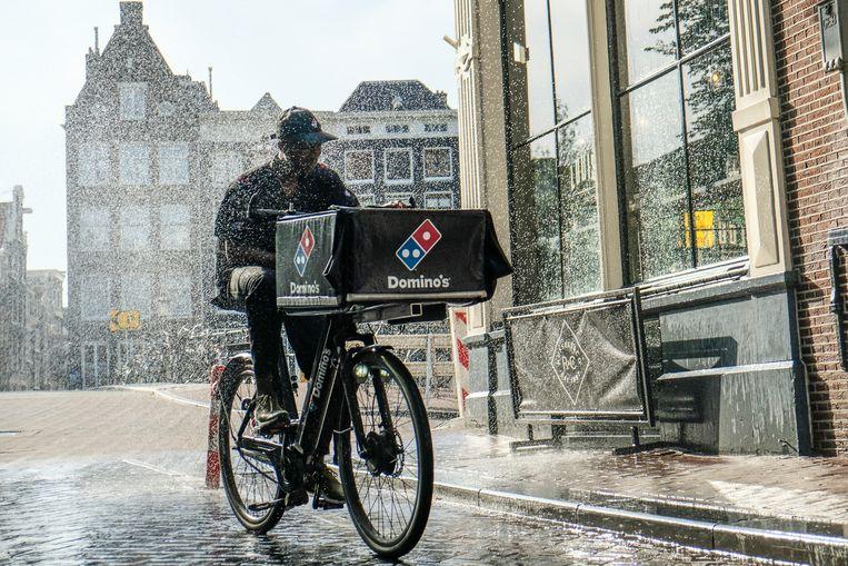 Buurtbewoners hebben voor een kort moment verkoeling gecreëerd voor een fietskoerier van Domino's. Beeld Hollandse Hoogte / Ingrid de Groot