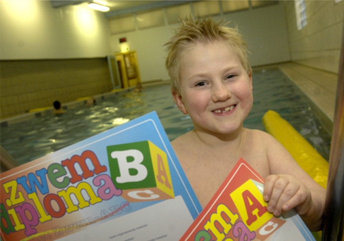 De aan zijn arm gehandicapte zevenjarige Samuel Massink uit Enschede poseert voor het succesvol afzwemmen voor zijn C-diploma met zijn eerder behaalde A- en B-diploma's. Foto Frans Nikkels