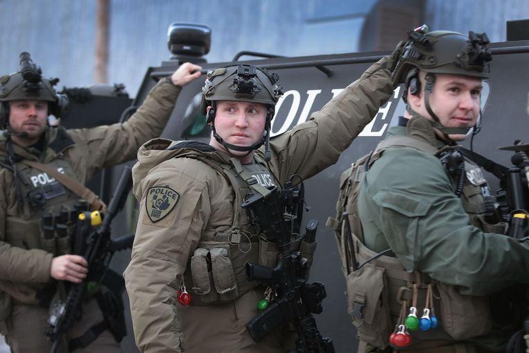 Zwaarbewapende politieagenten op de plaats van de schietpartij in Aurora bij Chicago. Beeld AFP